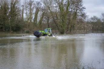 Tractor attempts to drive through flooded field homepage